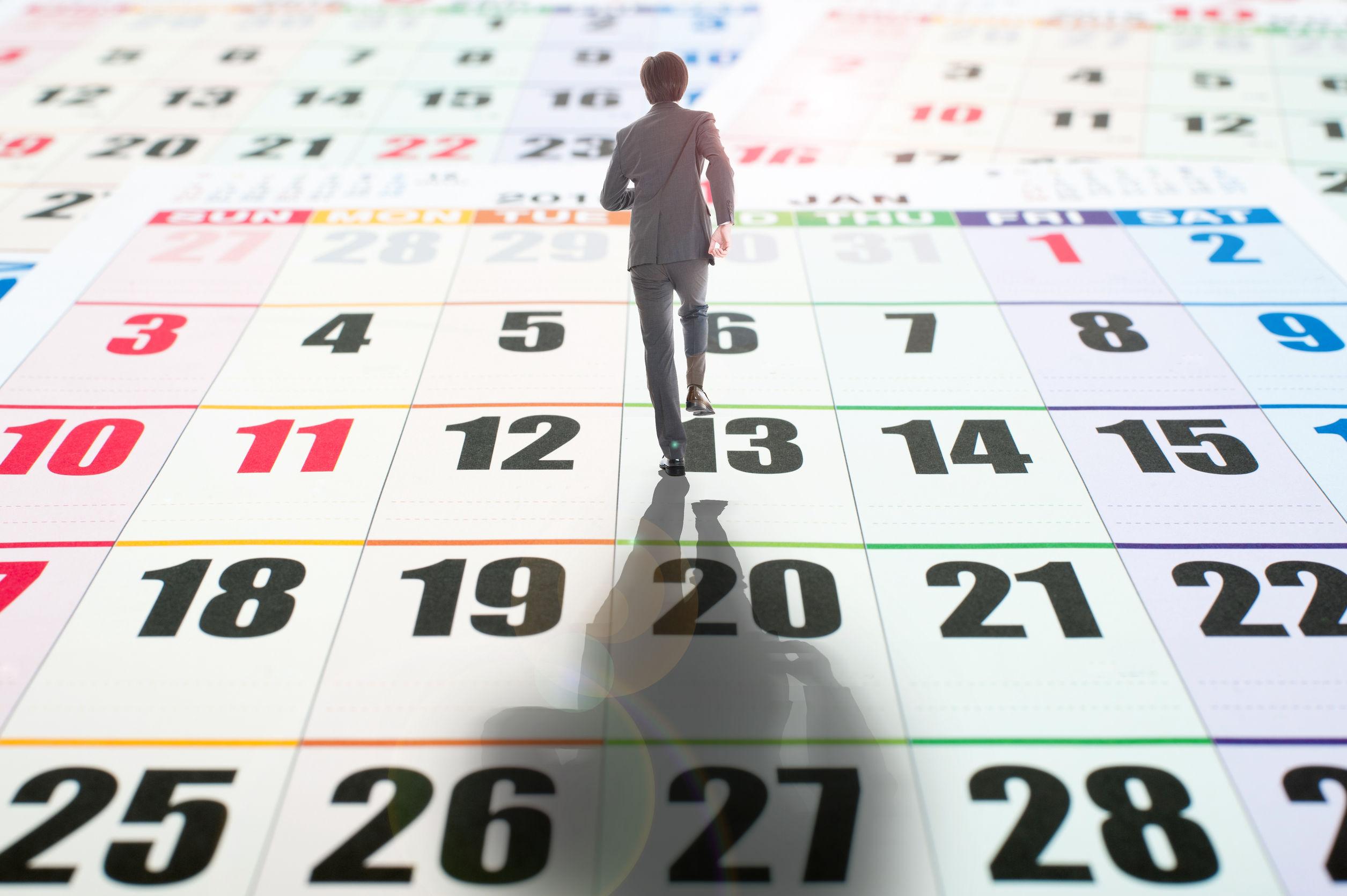 51950135 - businessman walking on the calendar