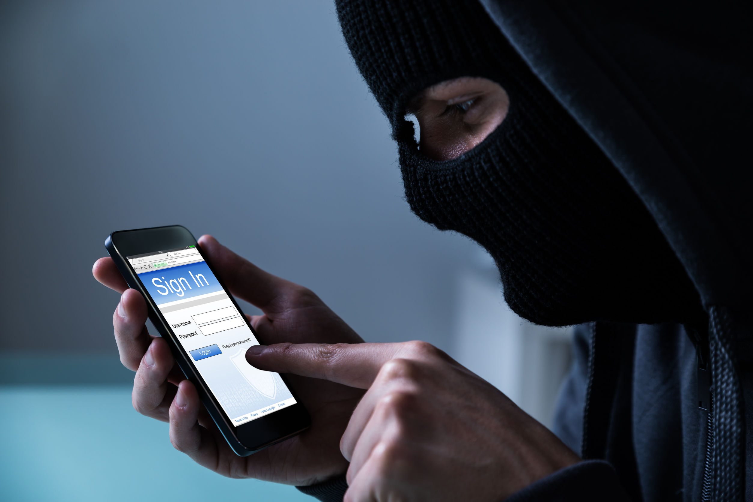 54598500 - close-up of hacker using smart phone to steal data in office