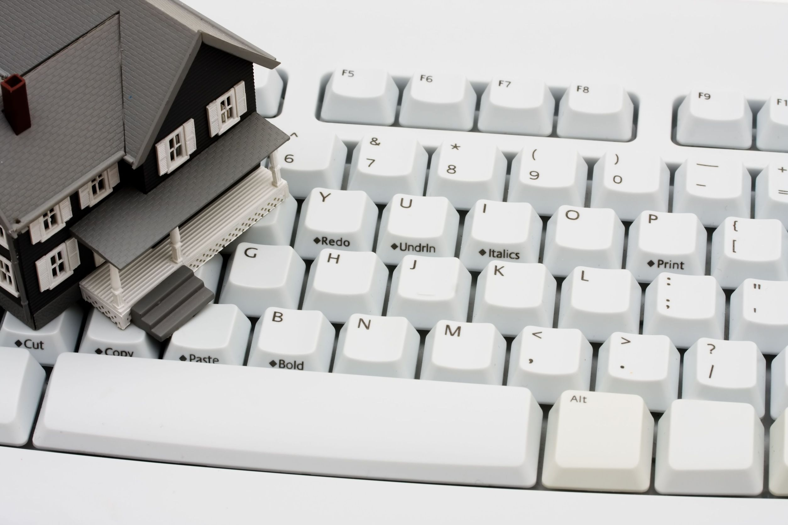 6377965 - a model house sitting on a computer keyboard, online real estate
