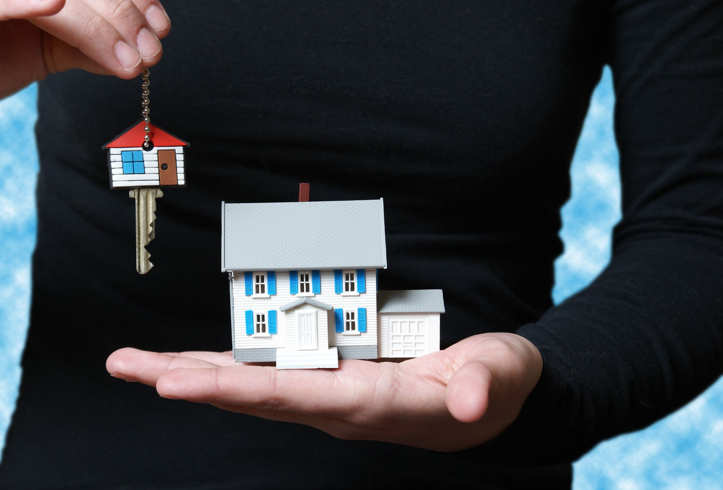8958769 - a conceptual image of someone receiving their key to their new home.
