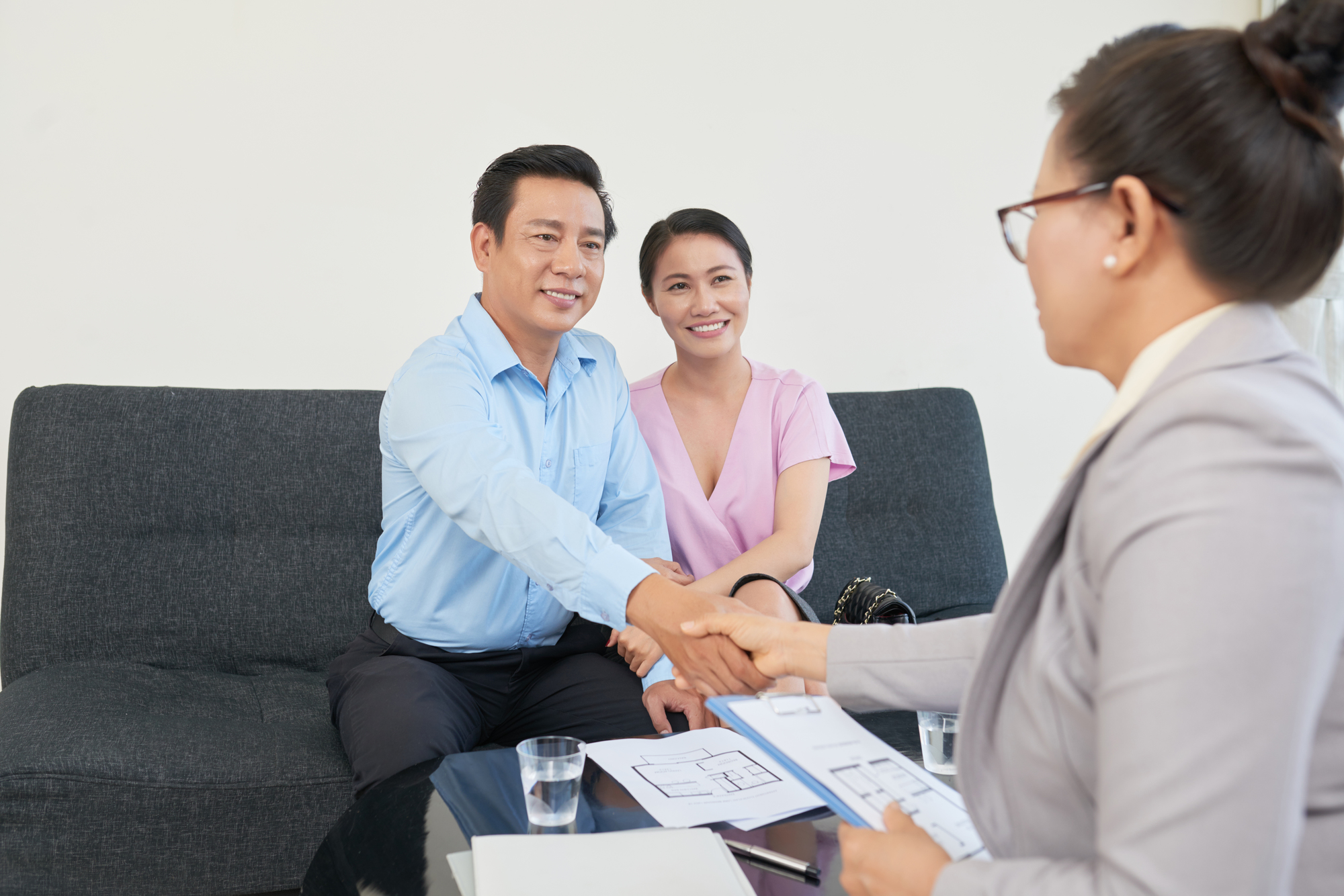 Happy mature couple meeting with realtor before buying a house
